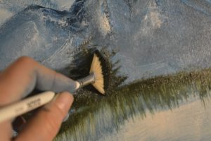 Use the fan brush to paint evergreens